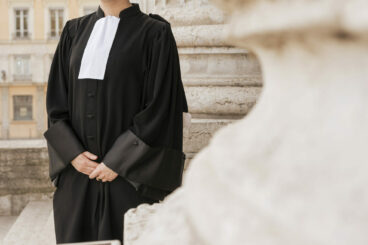 Un avocat en robe devant l'Ancien Palais de Justice de Lyon